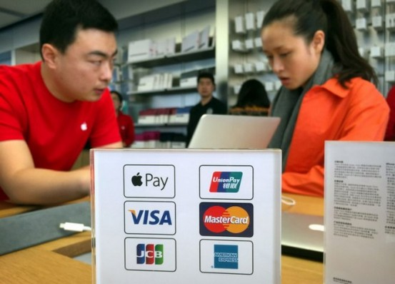 An employee works on a laptop computer as he talks with a customer near a sheet showing accepted methods of payment, including Apple Pay, top left, at an Apple Store in Beijing, Thursday, Feb. 18, 2016. Apple Inc. on Thursday launched its smartphone-based payment system in China where the electronic payments market is already dominated by an arm of e-commerce giant Alibaba. (AP Photo/Mark Schiefelbein)